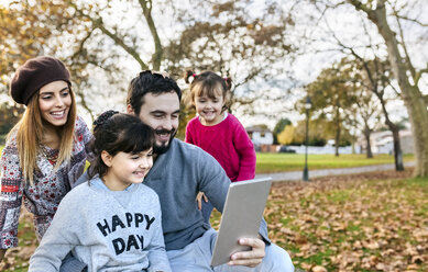 Family with tablet in autumnal park - MGOF03191