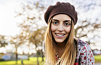 Portrait of smiling young woman wearing beret in autumn - MGOF03194