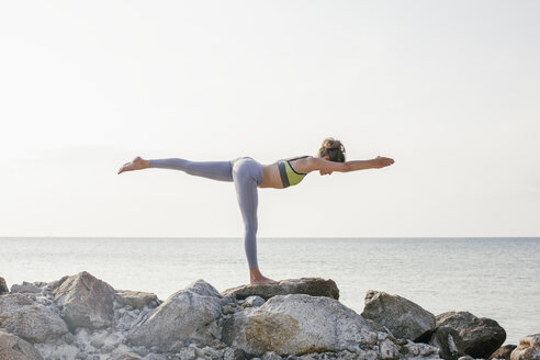 Woman practicing yoga on the beach - MOMF00059