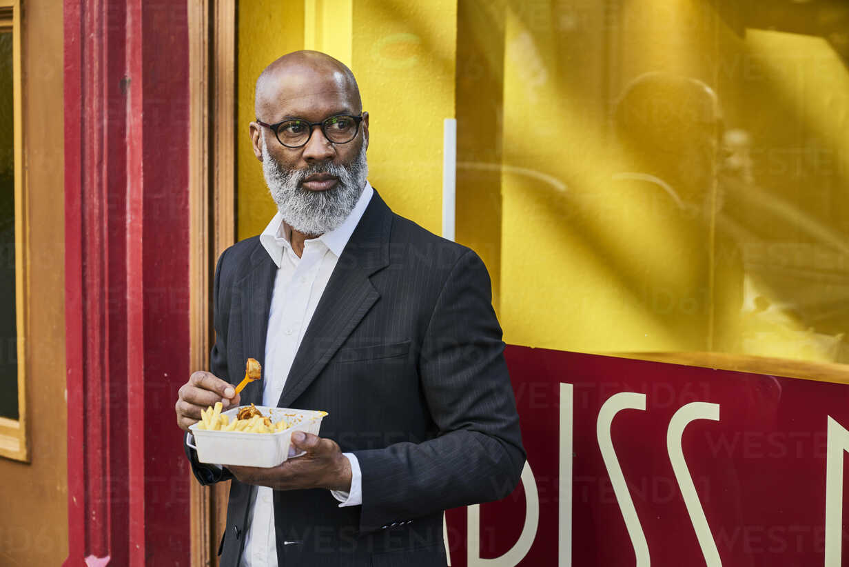 Mature businessman eating French fries in front of snack bar - FMKF03820 - Jo Kirchherr/Westend61