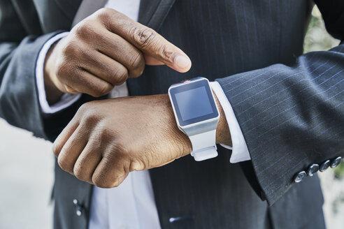 Mature businessman wearing smartwatch - FMKF03823