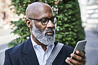 Mature businessman reading smartphone messages - FMKF03826
