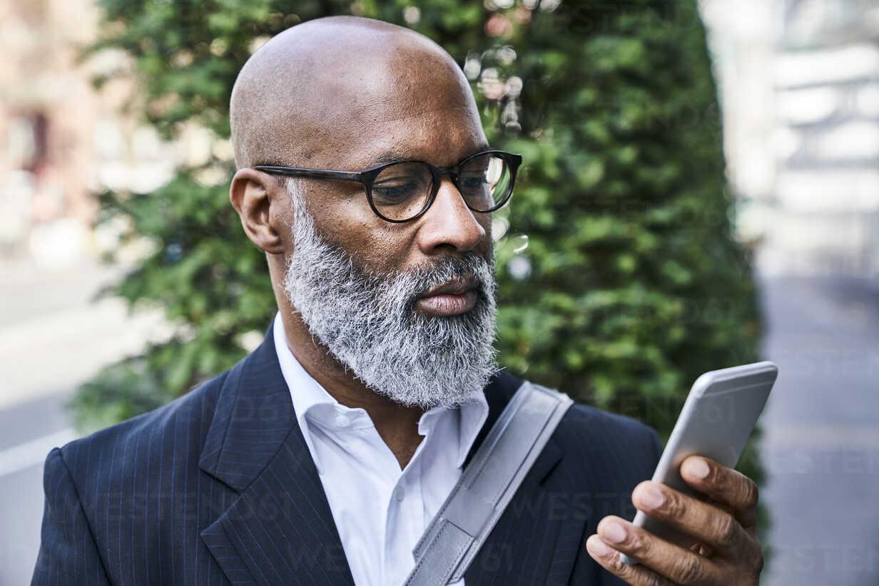 Mature businessman reading smartphone messages - FMKF03826 - Jo Kirchherr/Westend61