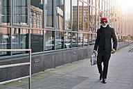 Mature businessman walking in the street - FMKF03832