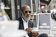 Mature businessman drinking coffee in pavement cafe - FMKF03850