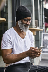 Mature man using smartphone in coffee shop - FMKF03856