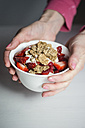 Woman holding bowl with muesli, yogurt and strawberries - CHPF00384