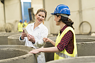 Female colleagues doing measurments in a factory, using digital tablet - JASF01590