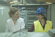Female colleagues working at control panel in a factory - JASF01599