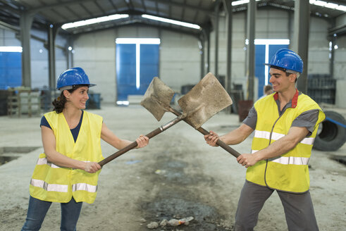 Factory workers playfighting with shovels - JASF01602