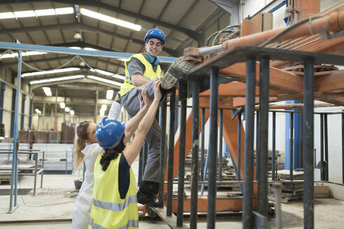 Workers repairing machine in concrete factory - JASF01608
