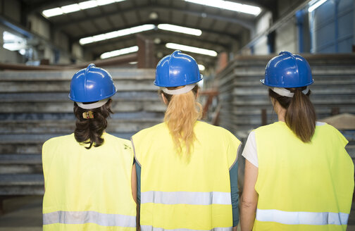 Three industry workers standing by steel girders in a row, rear view - JASF01617