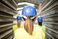 Three industry workers standing by steel girders, rear view - JASF01620