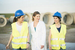 Female colleagues in a factory smiling at each other - JASF01635