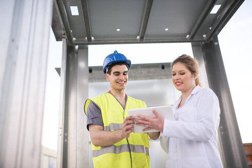 Scientist and factory worker looking at digital tablet - JASF01641