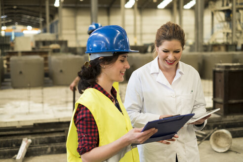 Women working together in concrete factory - JASF01647