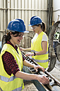 Female skilled workers in concrete factory adjusting machine - JASF01653