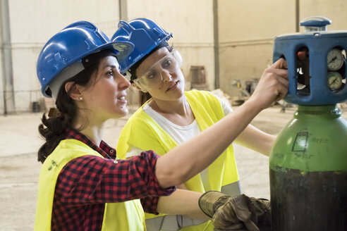 Female skilled workers in concrete factory adjusting welding torch - JASF01656