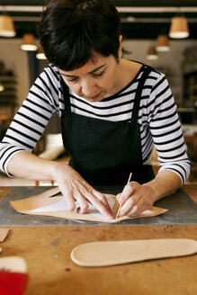 Shoemaker working on template in her workshop - VABF01300