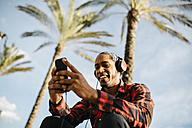 Spain, portrait of smiling young man listening music with headphones looking at cell phone - JRFF01289