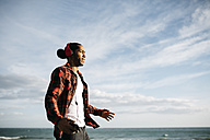 Young man walking in front of the sea listening music with headphones - JRFF01292
