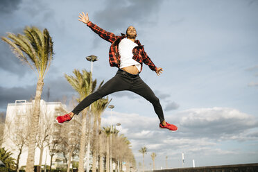 Spain, young man jumping in the air - JRFF01295