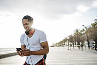 Spain, smiling young man with headphones on beach promenade looking at cell phone - JRFF01298