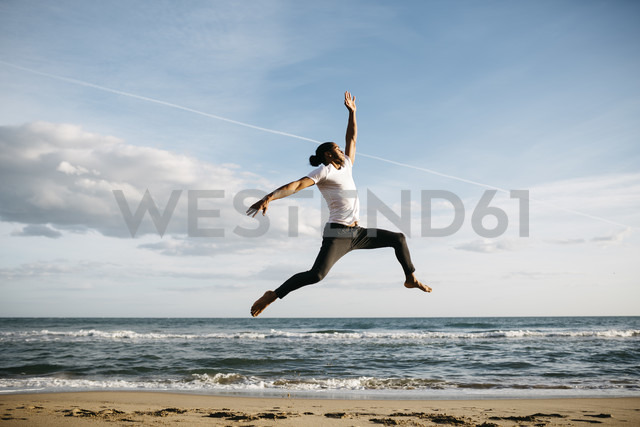 Young man jumping in the air on the beach - JRFF01301 - Josep Rovirosa/Westend61