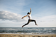 Young man jumping in the air on the beach - JRFF01301