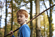 Portrait of redheaded boy with wood stick in the forest - JEDF00290