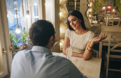 Portrait of smiling young woman talking to her boyfriend in a restaurant - MOMF00080