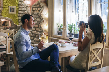 Young couple taking instant photos in a restaurant - MOMF00086