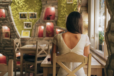 Back view of young woman sitting at table in a restaurant - MOMF00089
