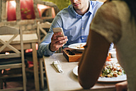 Man checking messages while having dinner in a restaurant - MOMF00107