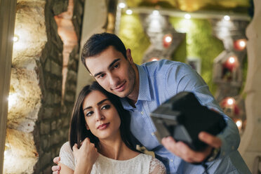 Young couple taking instant photos - MOMF00113