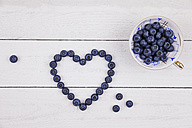 Collectors cup of blueberries and heart shaped with blueberries on wood - GWF05183
