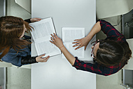 Two students learning together in a library - ZEDF00589