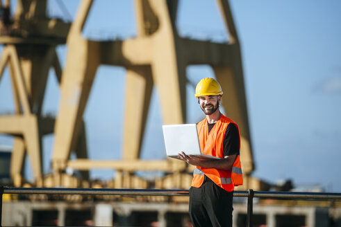 Portrait of smiling port worker using a laptop at work - KIJF01379