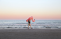 Young woman walking with inflatable pink flamingo on the beach at sunset - RTBF00812