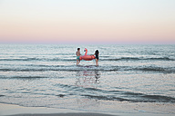 Back view of young couple walking into the sea with inflatable pink flamingo - RTBF00818