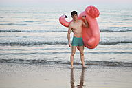 Young man with inflatable pink flamingo on the beach - RTBF00821