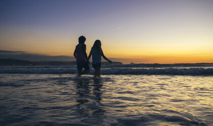 Young couple walking in the sea at dusk - DAPF00687