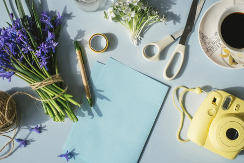 Sheets of paper, camera, scissors, cup of coffee and spring flowers on light blue background - MOMF00132