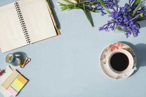 Notebook, office supplies, cup of coffee and spring flowers on light blue background - MOMF00135