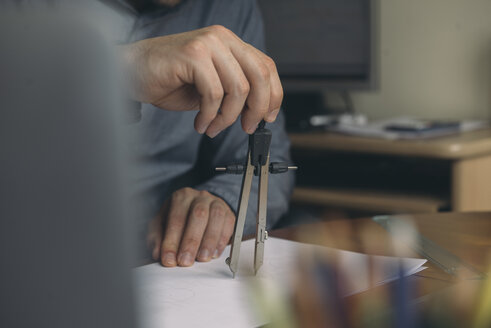 Close-up of man using compasses at desk - SKCF00286