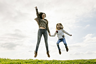 Happy mother and daughter jumping on a meadow - MGOF03225