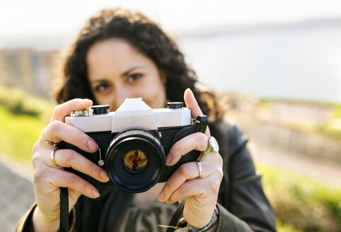 Portrait of a woman holding an old-fashioned camera outdoors - MGOF03231
