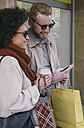 Happy couple in the city with cell phone and shopping bags - MOMF00146