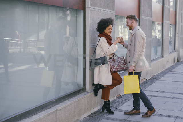 Happy couple in the city with takeaway coffee and shopping bags - MOMF00152