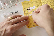 Hand putting sticker in vaccination pass - MFF03484